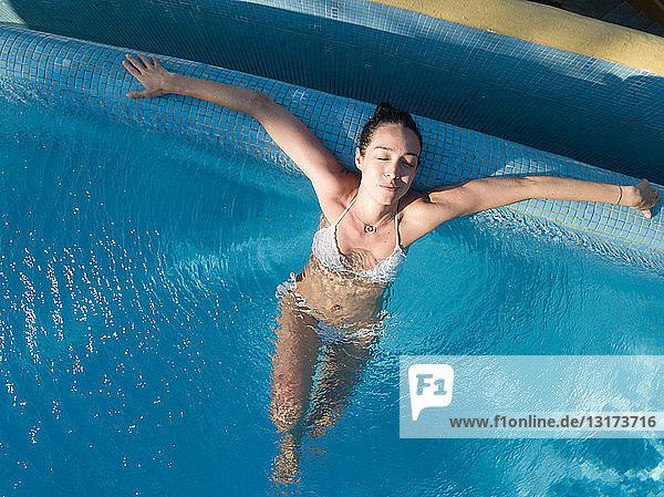 Woman enjoying bath in swimming pool  eyes closed