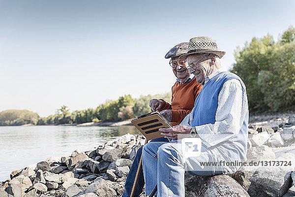 Zwei alte Freunde sitzen am Flussufer und benutzen ein digitales Tablett