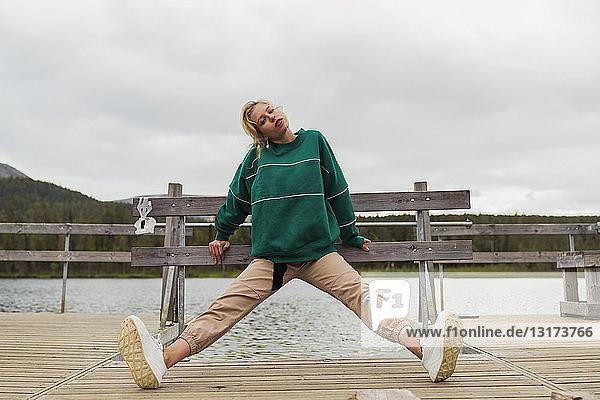 Finnland  Lappland  Frau  die sich auf einem Steg an einem See ausstreckt