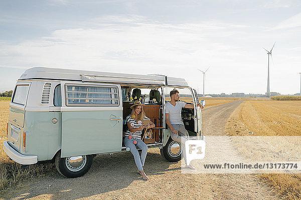 Junges Paar entspannt sich im Wohnmobil in ländlicher Landschaft