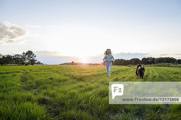 Girl with a dog running over a field at sunset
