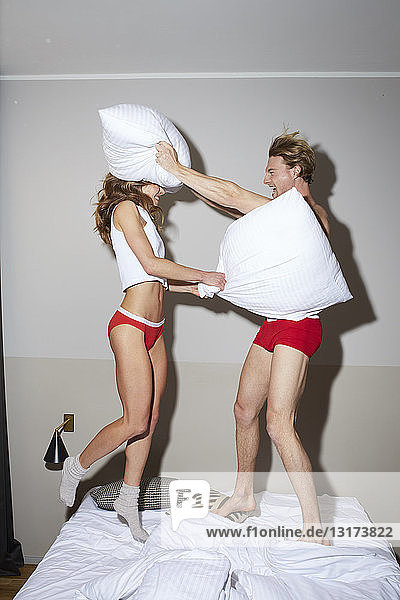 Couple having a pillow fight in bed
