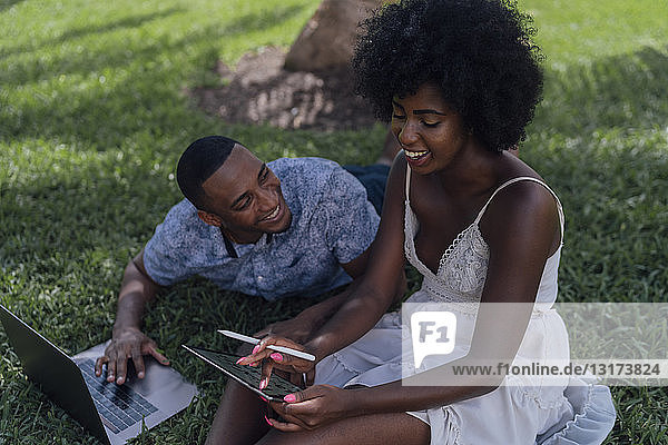 Happy young couple using tablet and laptop on lawn in a park