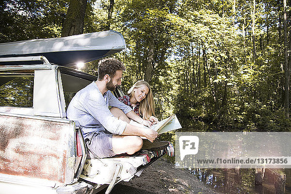 Smiling young couple with map and canoe in car at a brook