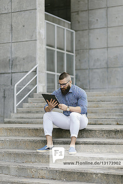 Bearded hipster businessman sitting on stairs using digital tablet