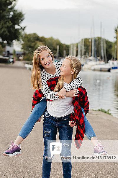 Mädchen nimmt ihren Freund Huckepack
