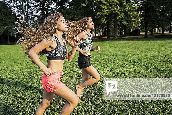 Zwillingsschwestern joggen barfuss in einem Park