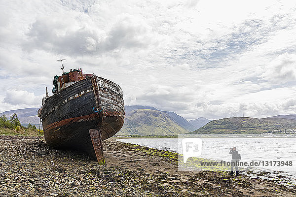 UK  Scotland  Highland  photographer taking picture of ship wreck at the beach of Corpach