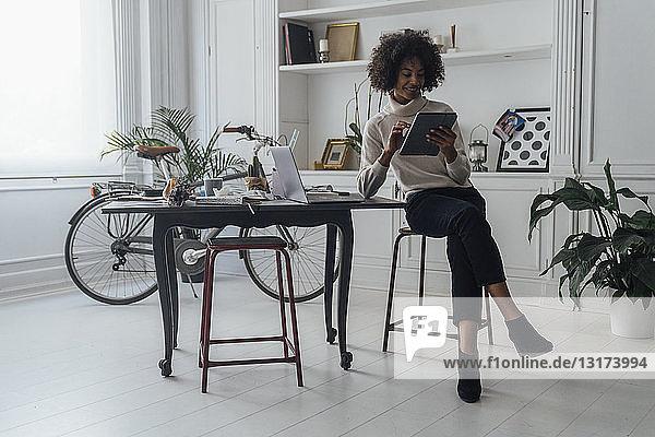 Mittlere erwachsene Freiberuflerin  die an ihrem Schreibtisch sitzt und mit Laptop und digitalem Tablett arbeitet
