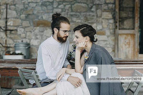 Liebevolle glückliche Braut und Bräutigam am Tisch sitzend