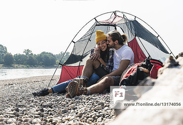 Glückliches junges Paar sitzt in einem Zelt am Flussufer