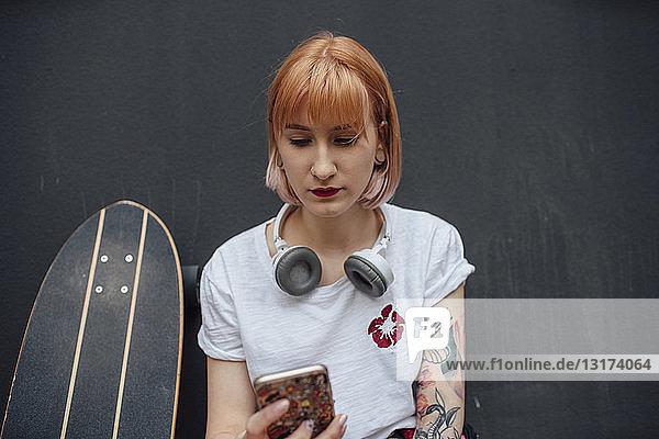 Junge Frau mit Skateboard und Kopfhörer beim Telefonieren