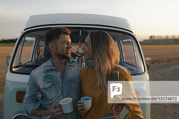 Happy young couple at camper van in rural landscape at sunset