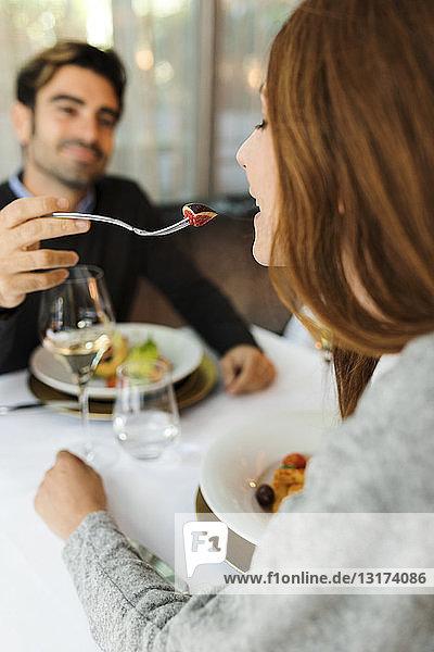 Mann lässt Frau das Essen in einem Restaurant kosten