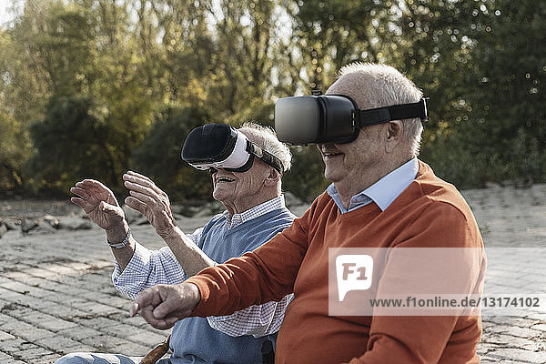 Two old friends sitting by the riverside  using VR glasses