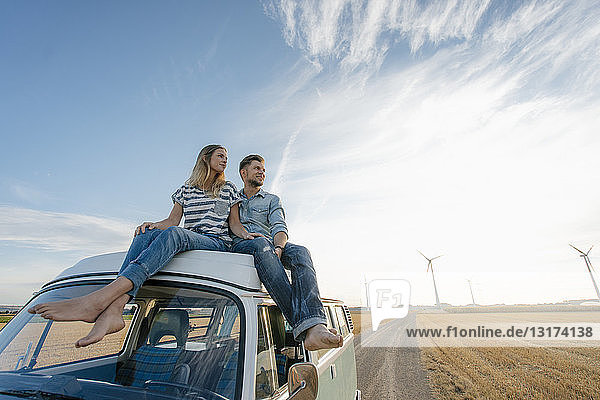 Couple sitting on camper van in rural landscape with wind turbines in background