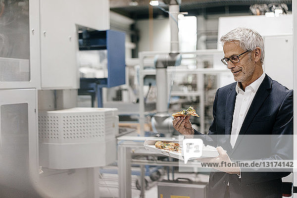 Manager in high tech company  eating pizza