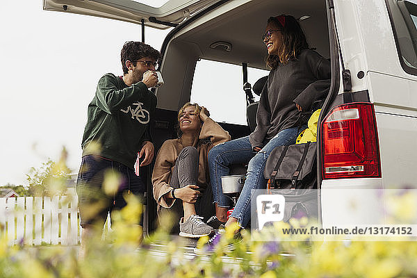 Freunde sitzen in einem Wohnwagen  machen eine Pause  trinken Kaffee
