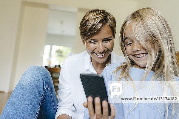 Glückliche Mutter und Tochter schauen sich gemeinsam ein Smartphone an