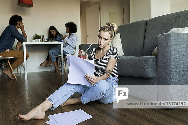 Young woman sitting on floor with papers and friends in background
