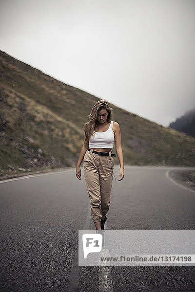 Blonde woman walking on a road  blurry person