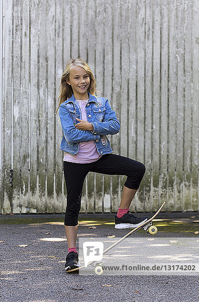 Portrait of smiling blond girl with skateboard