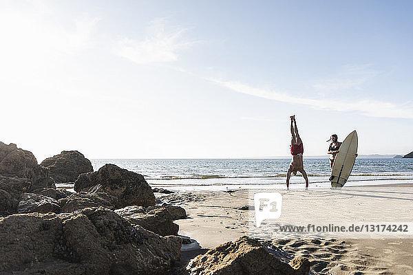 Frankreich,  Bretagne,  junger Mann macht einen Handstand und Frau hält ein Surfbrett am Strand