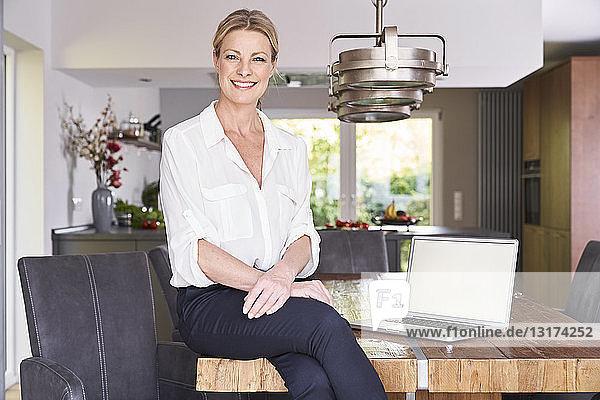 Porträt einer lächelnden Geschäftsfrau zu Hause  die mit Laptop am Tisch sitzt