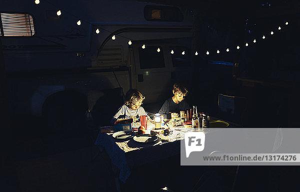 Brasilien  Bonito  zwei Jungen  die im Dunkeln im Wohnwagen zeichnen