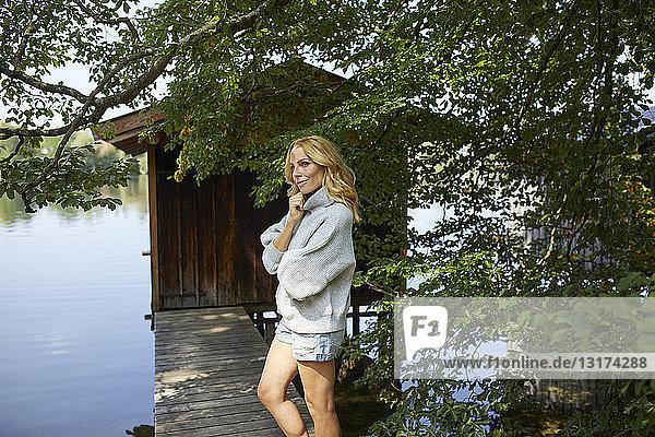 Frau steht auf Steg mit Holzhütte an einem See