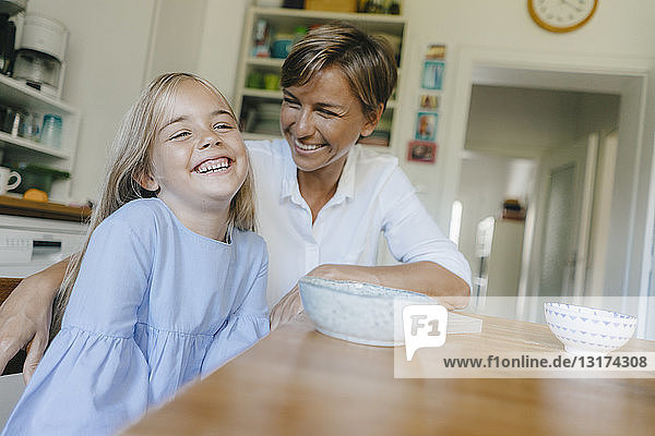 Happy mother and daughter sitting at kitchen table at home