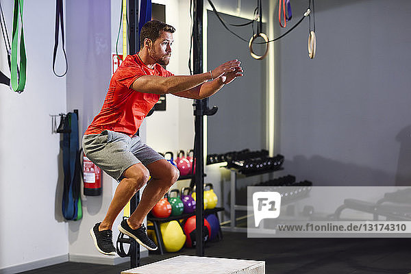 Man doing box jumps in a gym