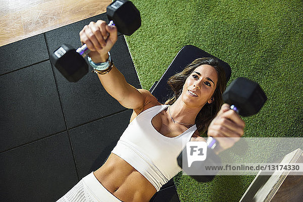 Woman training with dumbbells in a gym