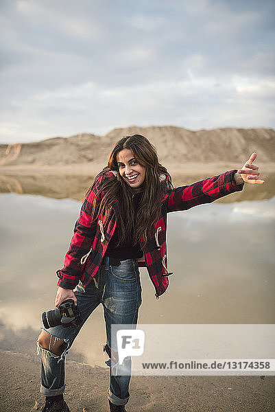 Portrait of laughing young woman with camera on the beach