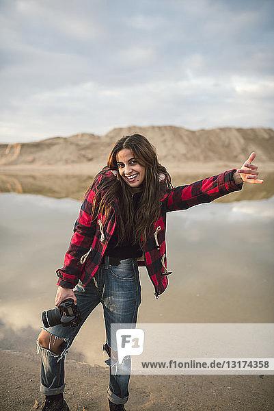 Porträt einer lachenden jungen Frau mit Kamera am Strand