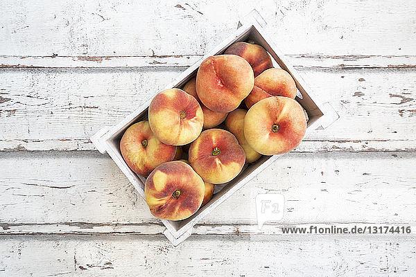 Doughnut-Pfirsiche in Holzkiste auf weißem Holz