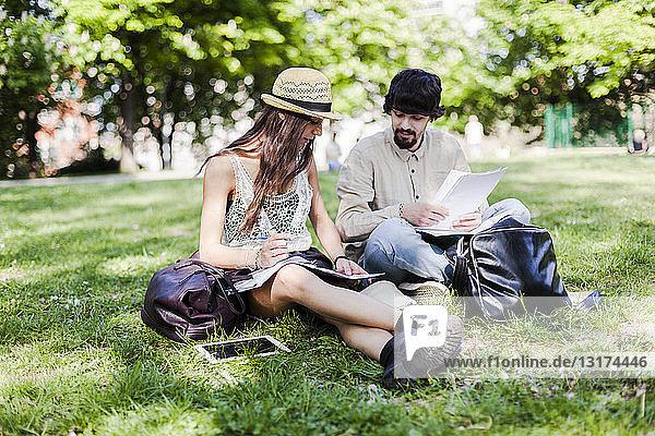 Zwei Studenten sitzen auf einer Wiese in einem Park und schauen sich Notizen an