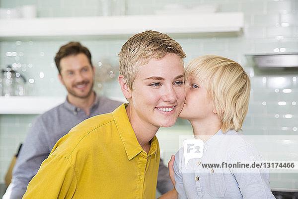 Sohn küsst Mutter in Küche mit Vater im Hintergrund