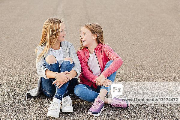 Zwei lächelnde Mädchen sitzen nebeneinander auf dem Boden