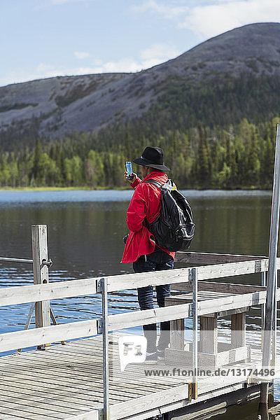 Finnland  Lappland  Mann macht Handyfoto am Seeufer