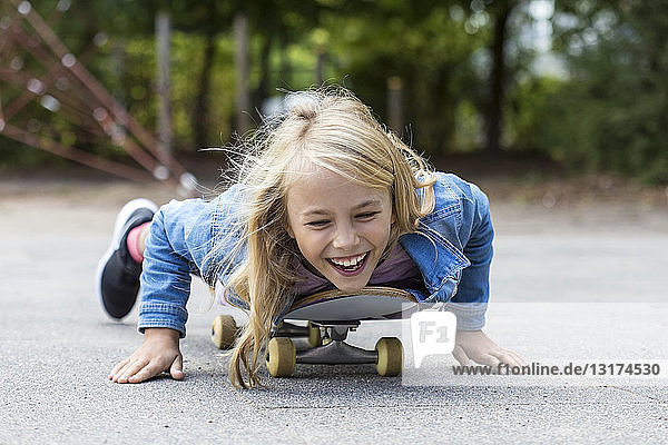 Portrait of laughing blond girl lying on her skateboard outdoors