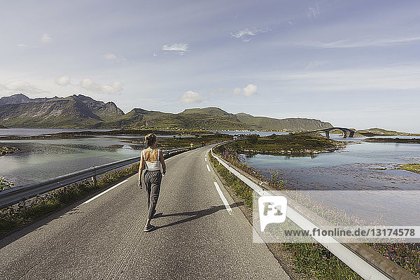 Young woman walking on an empty road  Lapland  Norway