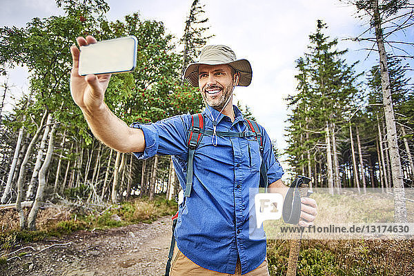 Man taking a selfie with his cell phone during hiking trip