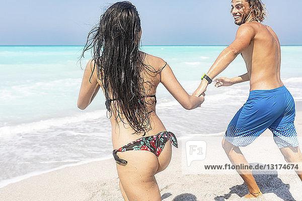 Paar am Strand  das ins Meer läuft und sich an den Händen hält