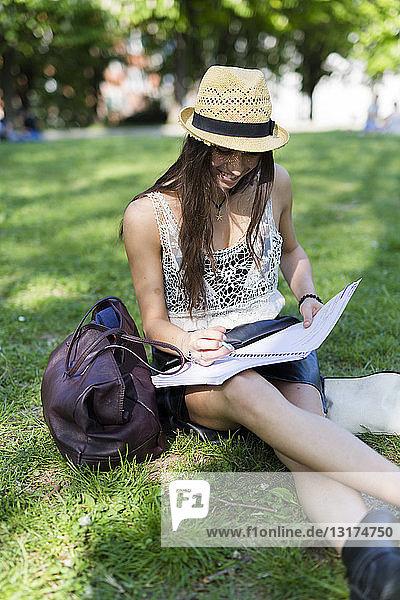Lächelnder junger Student sitzt auf einer Wiese in einem Park und benutzt ein Heft
