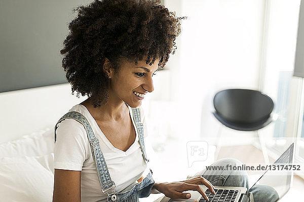 Lächelnde Frau sitzt mit Laptop auf dem Bett