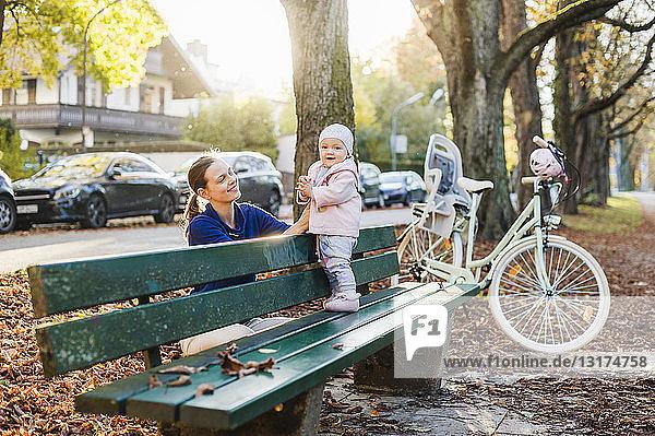 Mutter und Tochter machen eine Pause auf einer Parkbank