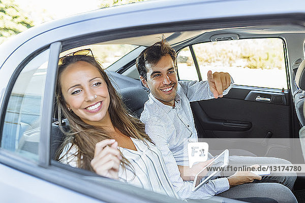 Smiling couple on back seat of a car looking out of window