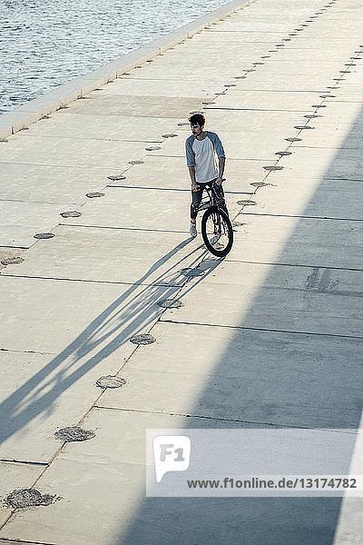 Junger Mann mit Pendler-Fixie-Fahrrad macht auf Uferpromenade am Fluss eine Pause