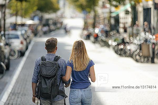 Niederlande  Maastricht  Rückansicht eines jungen Paares  das durch die Stadt läuft